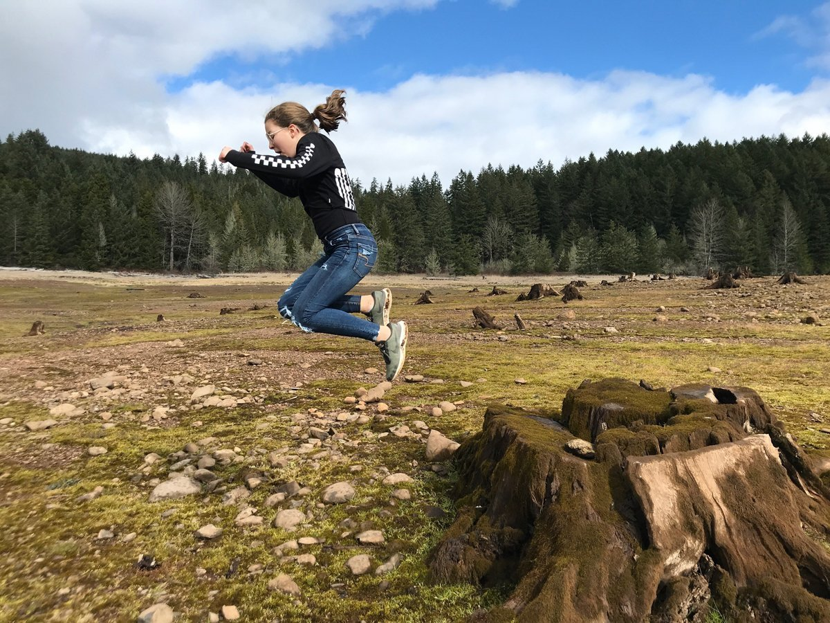 Jumping off a stump in the empty Fall Creek Lake while on a winter hike